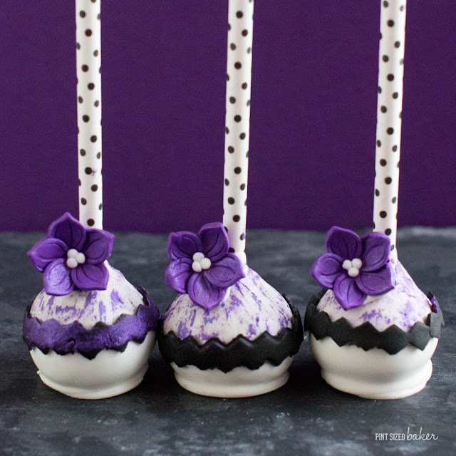 Pops of purple add a sophisticated fashion to these cake pops. A basic black and while ensemble with stunning purple posies.
