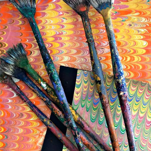 paint brushes displayed on marbled paper sheets