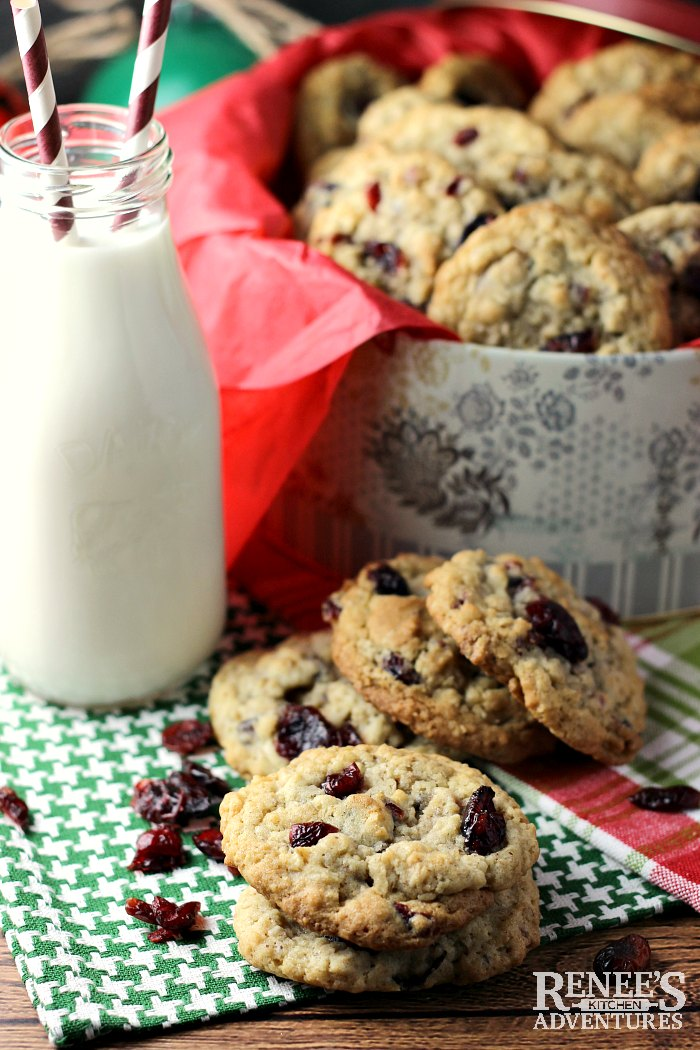 Oatmeal Cookies with Cranberries and Walnuts with milk, in tin, and scattered in front of tin