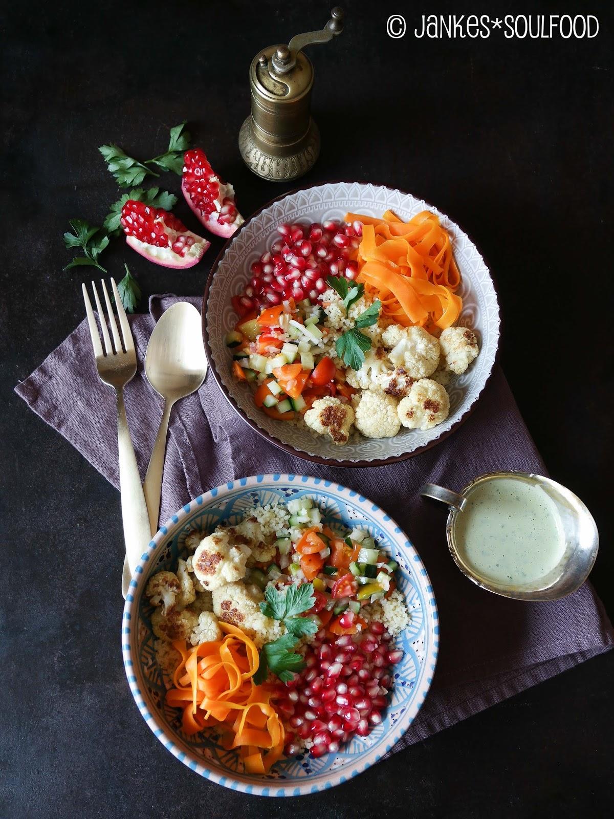 Bowl mit Couscous, Blumenkohl, Granatapfel und Tahinisauce