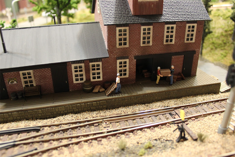 Dock workers from a Woodland Scenic Accents kit carry a crate at a POLA freight station kit
