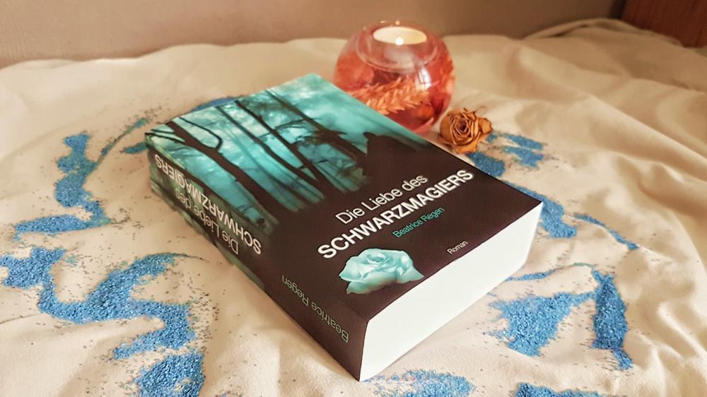Buch mit Kerze und Rosenblüte