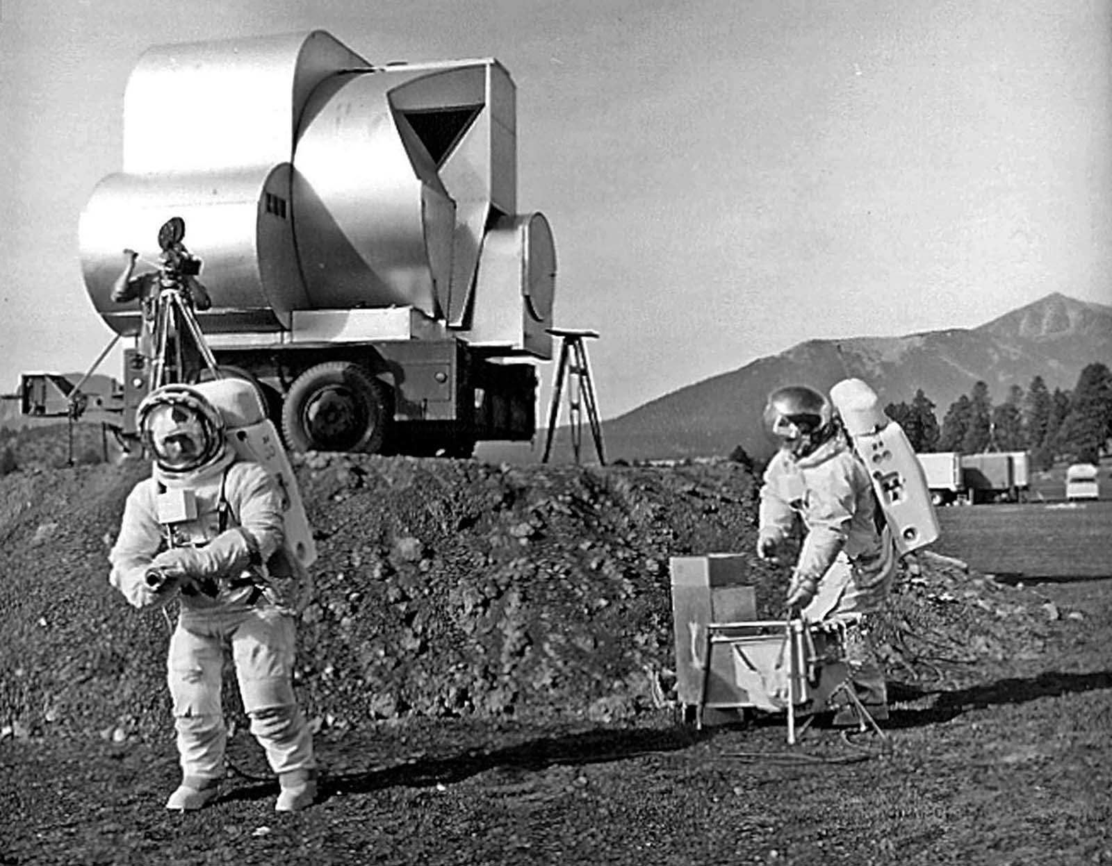 The USGS geologists Tim Hait and David Schleicher work in spacesuits during an early Apollo field test at Cinder Lake Crater Field #1, with a simulated lunar-module ascent stage mock-up parked on an earthen ramp in the background.