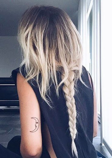 Uma simples personificação da lua crescente é mostrada na parte de trás do utente do braço esquerdo desta tatuagem.