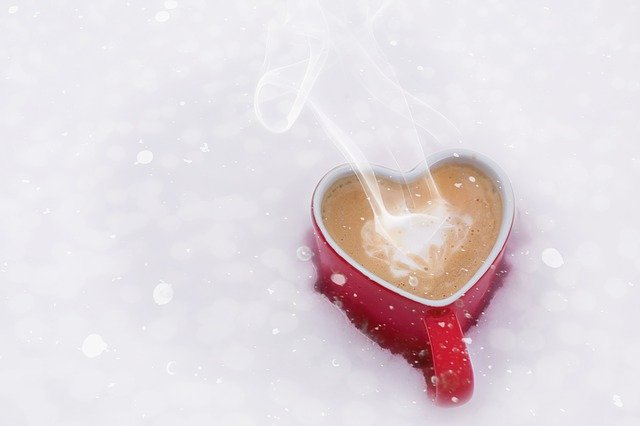 Heart shaped mug of hot coffee in the snow