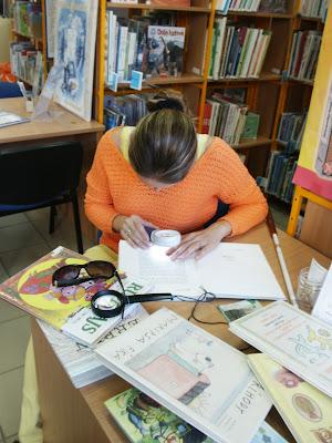 Linda sedí za stolem a čte pomocí lupy text v knize
