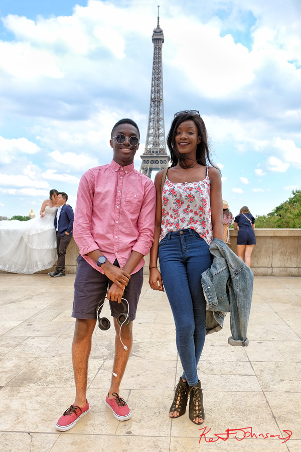Street style. A couple at the Place du Trocadéro with Tour Eiffel in background. He wears a pink button down shirt with navy shorts, pink runners and round sunglasses, she wears blue jeans and a floral roses singlet top, denim jacket held, sunglasses on the top of her head. Street Fashion photographed by Kent Johnson for Street Fashion Sydney.