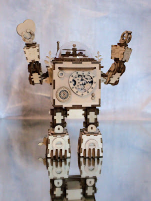 A wooden robot with his arms raised high, holding a heart in one hand.