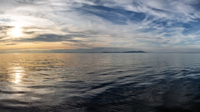 Photo of the sun going down over the Solway Firth with the Scottish hills in the distance