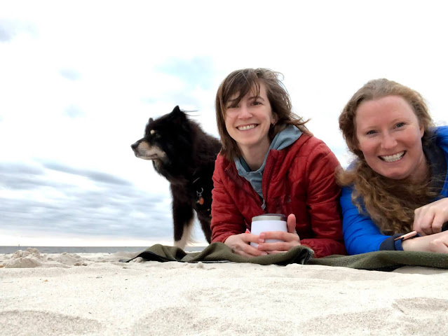 dog and two women on a beach