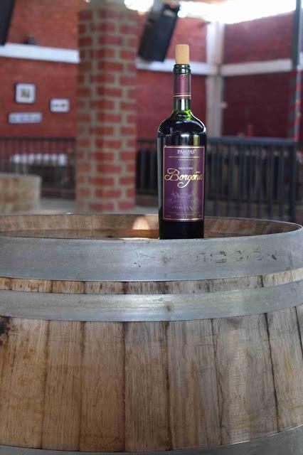 garrafa de vinho tinto em cima de um barril de madeira