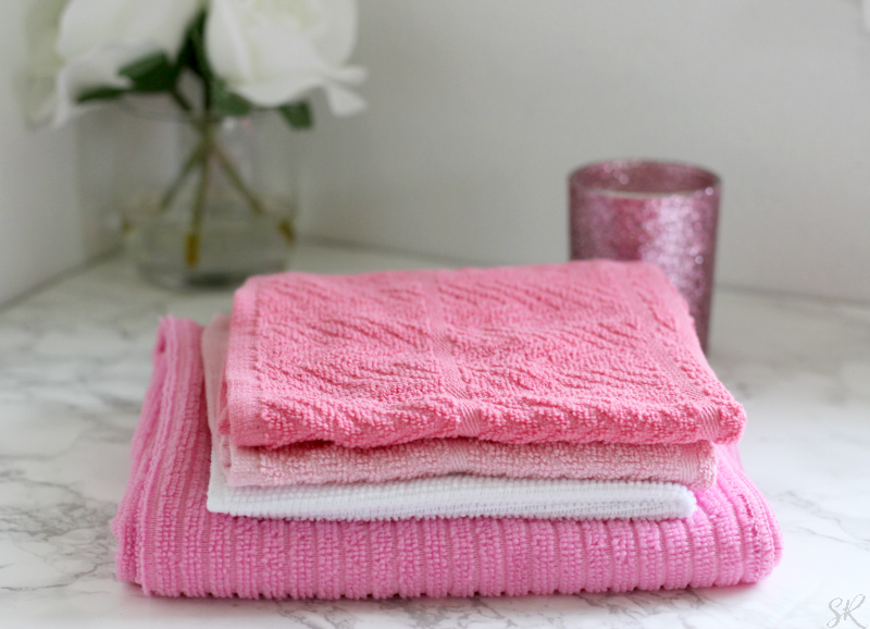 pink bath towels on a marble counter