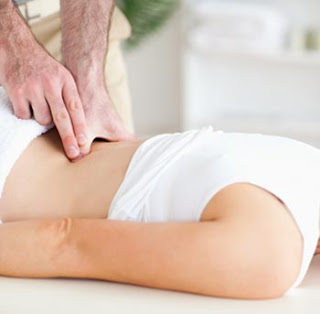 Chiropractor adjusting a patient's lower back to relieve pain.