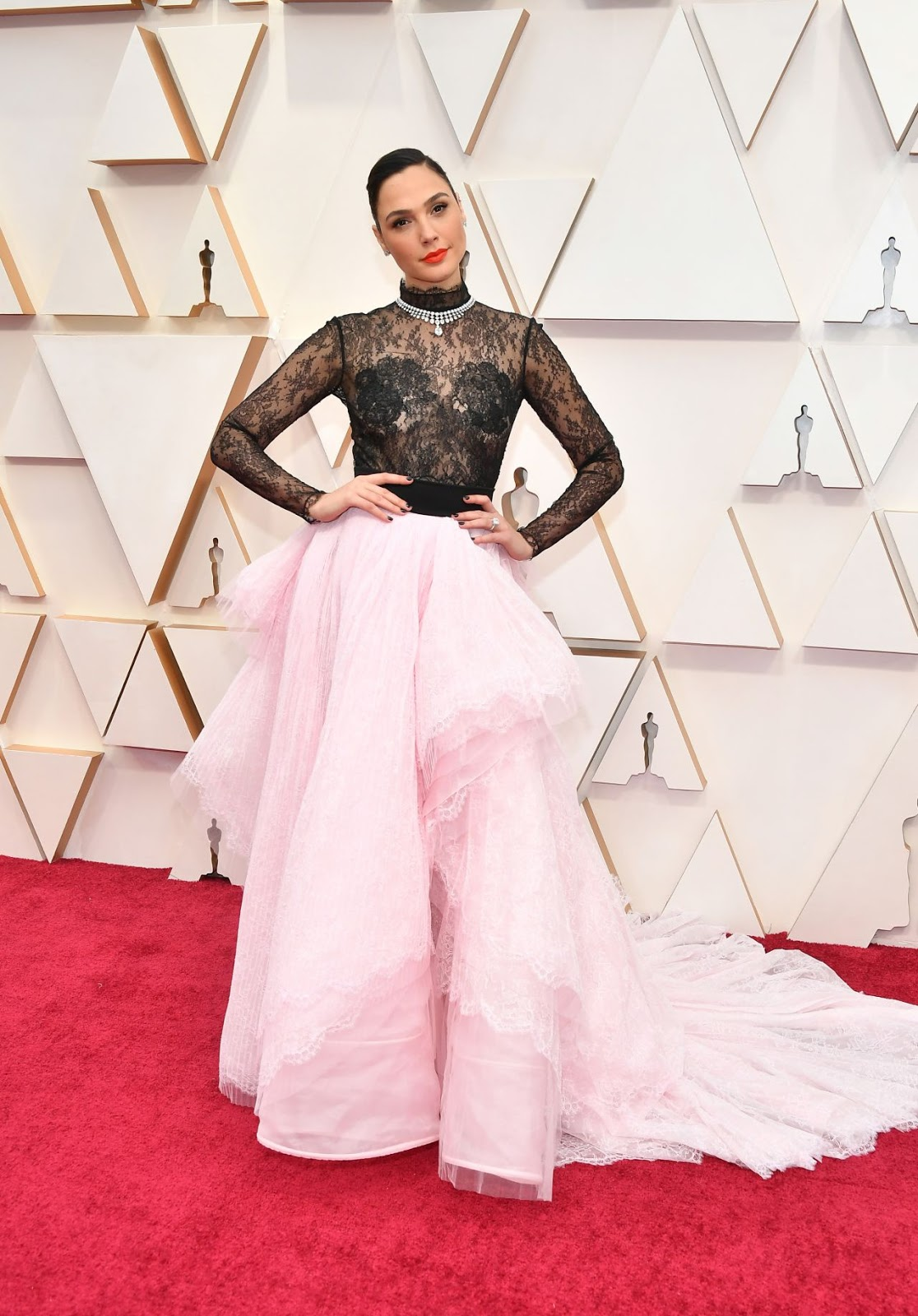 Gal Gadot wore a Givenchy Spring 2020 Haute Couture black lace bodysuit + pink silk organza skirt with lace petal ruffles to the 2020 Academy Awards.