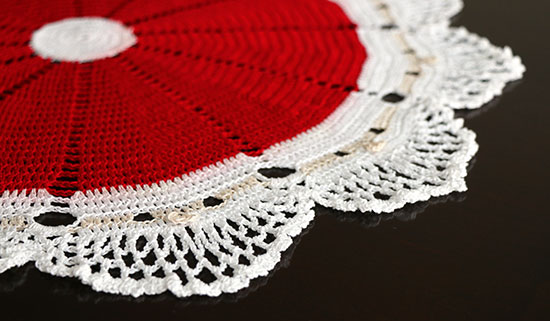 Detail of crocheted cotton doily made from 12 Santa faces with red hats on a dark background.