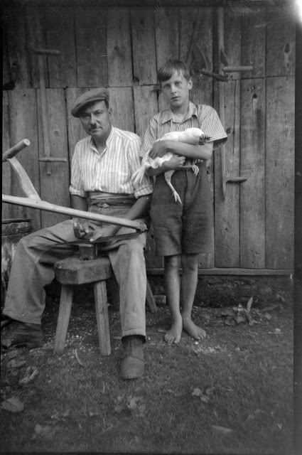 Vater beim Schleifen der Sense - Sohn mit Huhn - 1930-1953