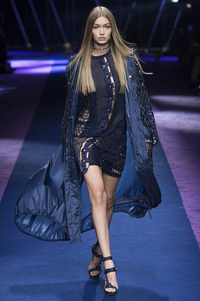 Gigi Hadid goes braless in a sheer navy dress as she storms the runway alongside younger sibling Bella at the Versace SS17 show for MFW