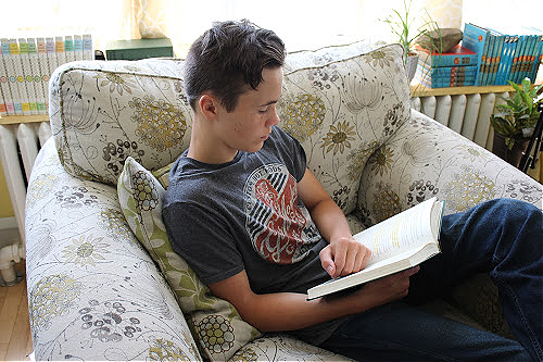 Teenage boy reading a book