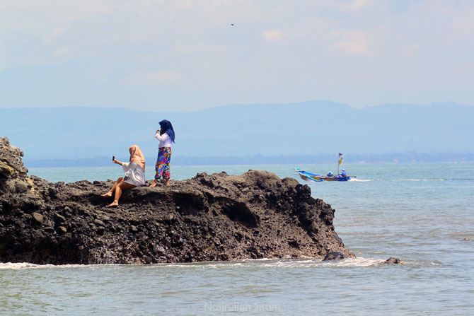Berfoto di bongkahan batu ujung pantai