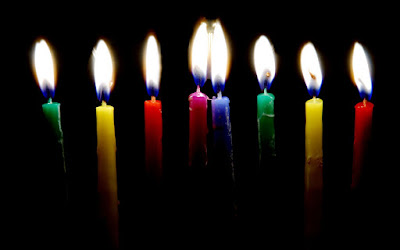ID: lit candles against darkness form a rainbow from left to right with green, yellow, red, purple, blue, green, yellow, and red