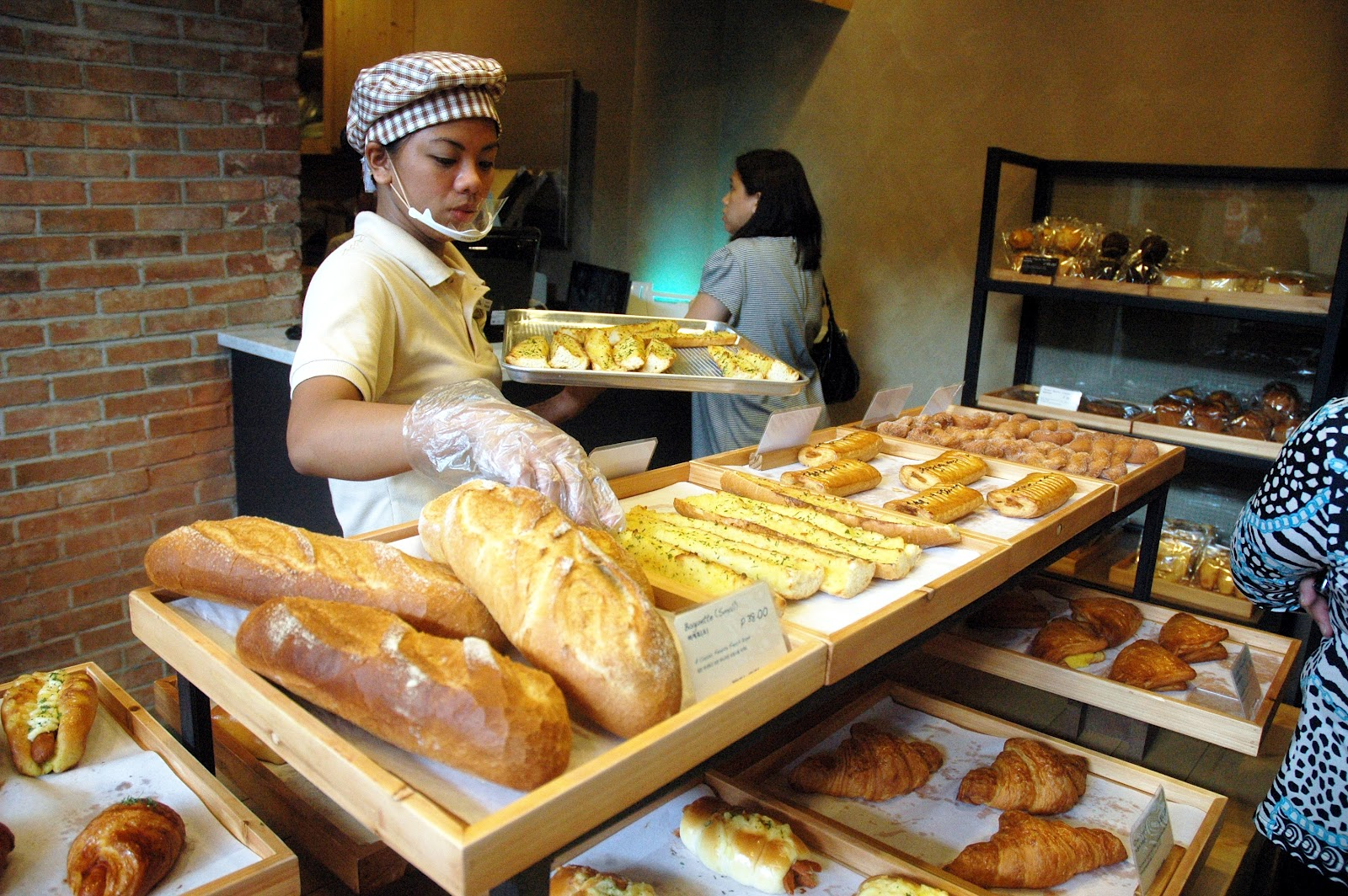 Image of a bakery sales clerk putting breads on display