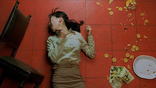 Girl lies screaming on a red tile floor with an overturned chair on the left and spilled cookies on the right