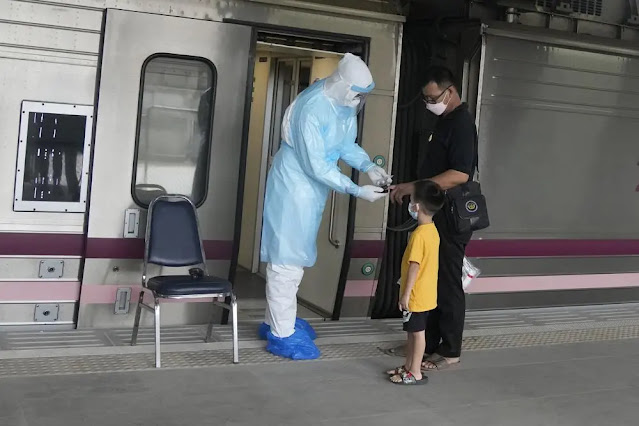 Medical staff check the oxygen levels of a person with COVID-19 at a train station in Pathum Thani province (Thailand) on July 27. Photo: AP