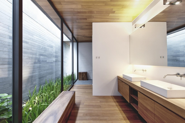 Glass wall in the bathroom of The Wall House by FARM Architects