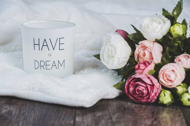 """There is a white votive candle which says """"I have a dream"""". The candle is next to a bunch of flowers and is sitting on a while cloth"""