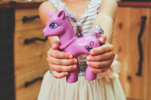 young girl holding a toy horse