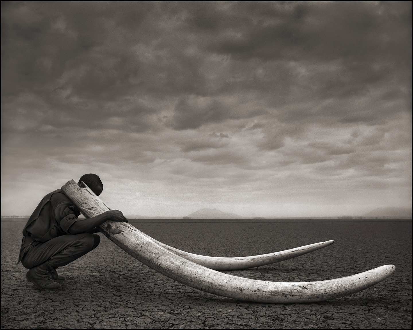 ©Nick Brandt, Ranger with Tusks of Dead Elephant, Amboselli, 2011.
