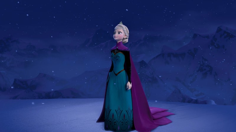 Elsa in dress, cloak, and tiara standing in a stark, icy setting as it snows