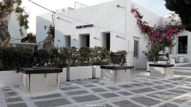 na placu Mykonos trzy białe studnie z metalowym kołowrotem w tle przy białym budynku kwitnący na różowo kącicierń
