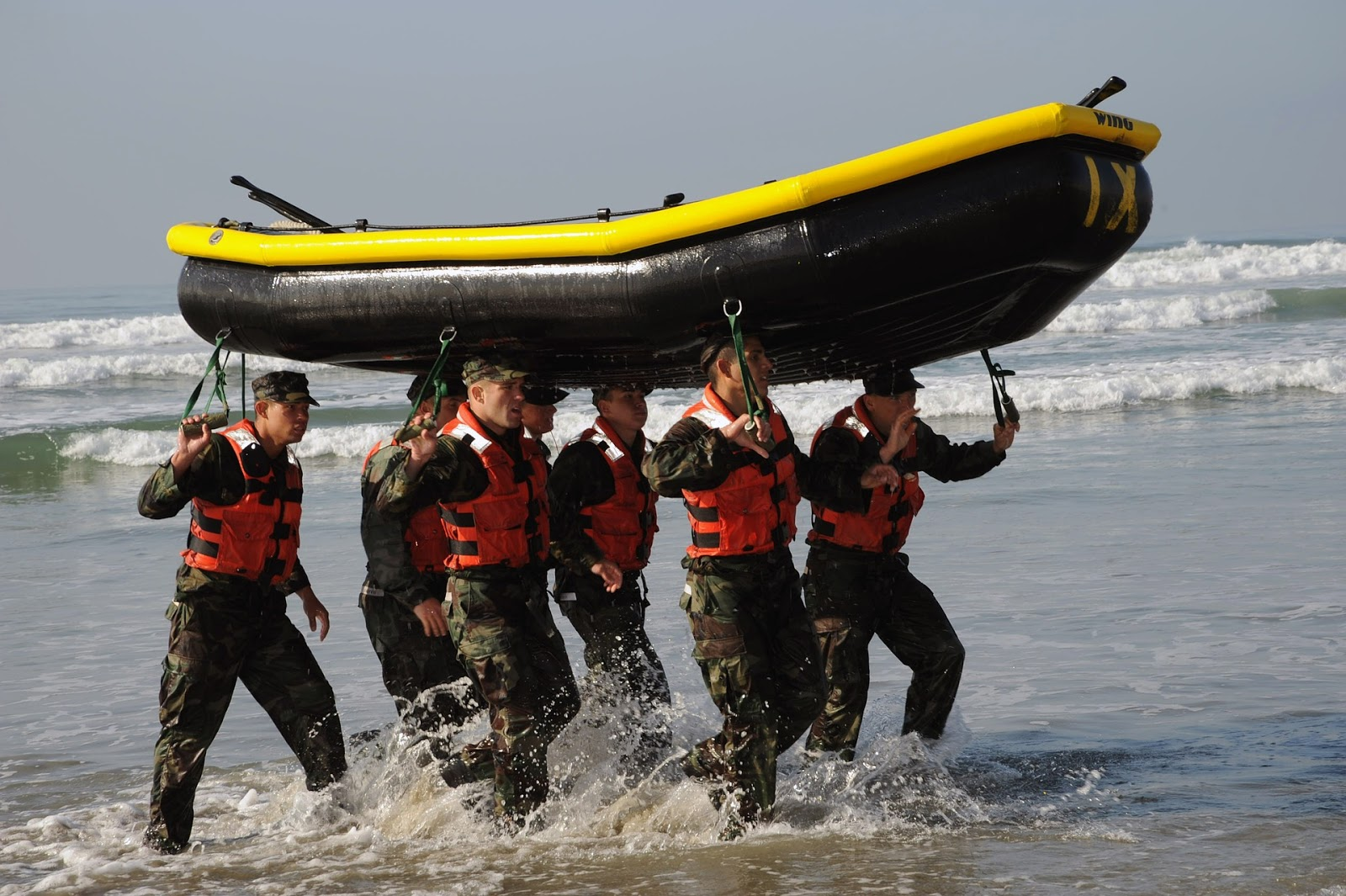 navy seals training by carrying black rubber boat on head to illustrate blog post about navy SEAL training