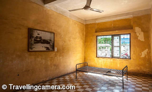 Before the Khmer Rouge's reign started, this building was a high school. Within 4 months of Khmer Rouge winning the Cambodian Civil War, the building was converted into a prison and interrogation center. Class rooms were converted to torture chambers and holding cells, where the prisoners were kept captive in inhuman conditions. Nearly 17000 prisoners passed through this prison between 1975-1979. Today, some relics of those terrible times still remain in the museum. This room, in the photograph above, was a torture chamber. When Vietnamese army discovered this prison in 1979,  they found a prisoner tied to the bed in the room. The prisoner had apparently died during interrogation and the body was already decomposing when the prison was discovered. The photograph of the body as it was discovered still hangs here.