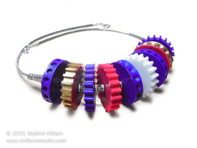 Big, bold, purple, gold, red and white resin cogs in a choker style necklace