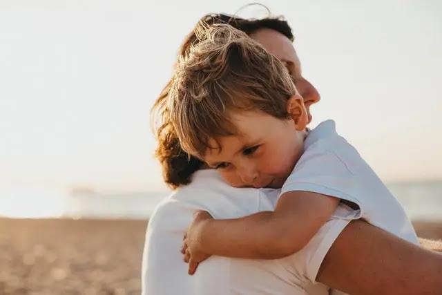 Mujer cargando y abrazando a un niño