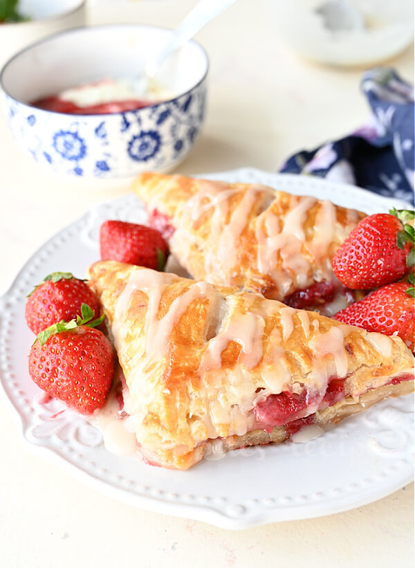 a white plate with fresh strawberries and strawberry turnovers
