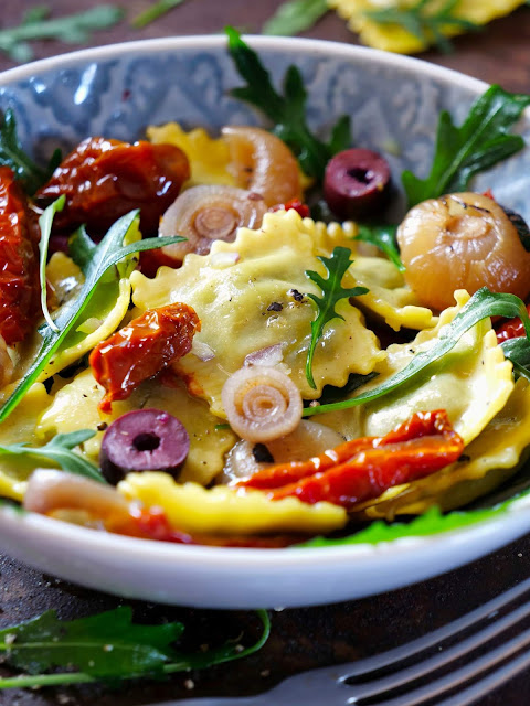 Ravioli-Salat mit Borrettane-Zwiebeln, getrockneten Tomaten, Rucola, Oliven und Salsiccia.