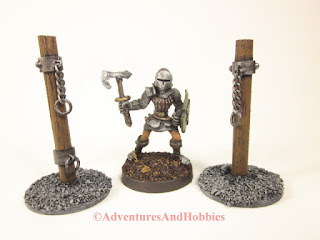Medieval knight with battleaxe standing between two pillory posts with chains in 25mm scale.