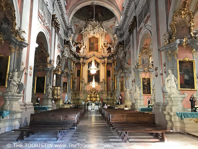 Pastel ornate interior and view towards the altar at Saint Theresa church in Vilnius in Lithuania