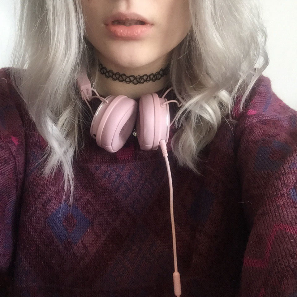 girl with grey hair wearing headphones and vintage jumper