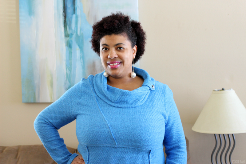 a black woman wearing a turquoise sweater