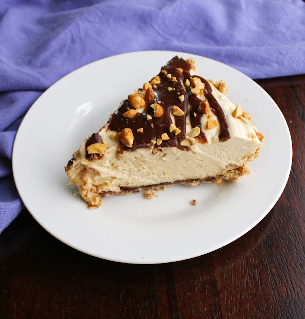 slice of creamy no bake peanut butter pie with drizzle of fudge and chopped peanuts on top