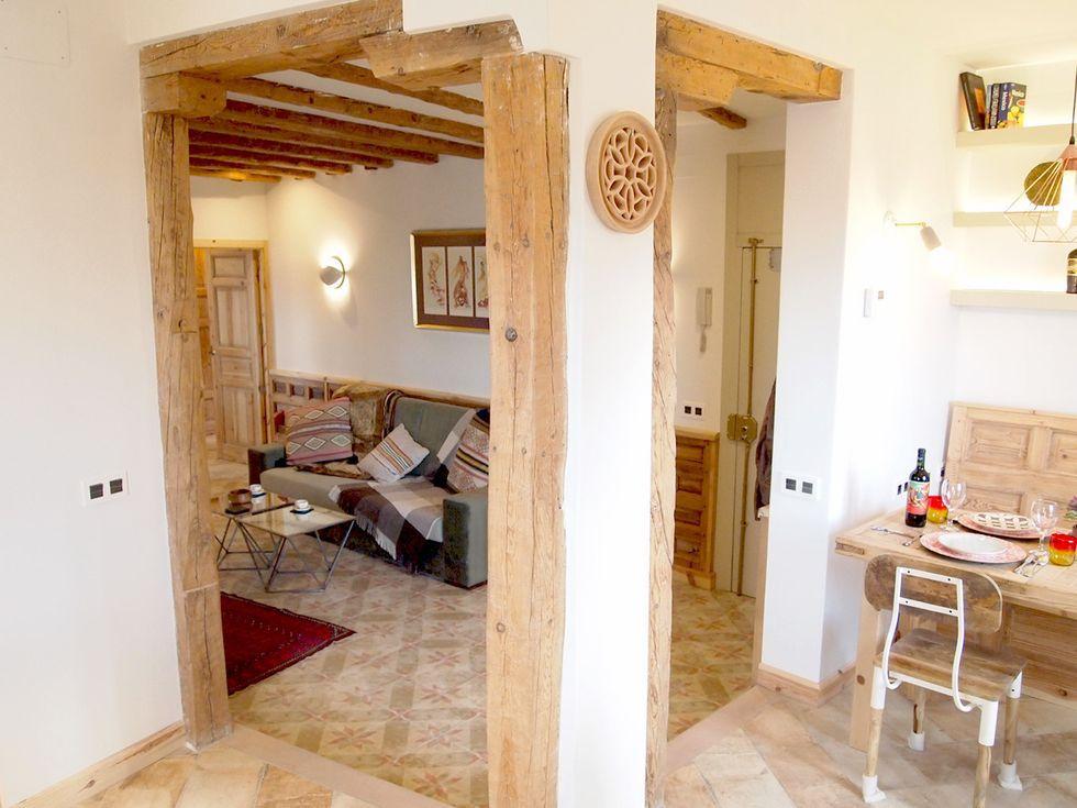 Acceso al salón y el comedor por vanos abiertos rematados con madera recuperada