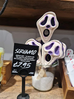 A screaming skeleton mask shaped white, purple and black bubble bar on a large wide light brown stick in a light brown square box with a black card that says scream bubble blower in light white font on a bright background