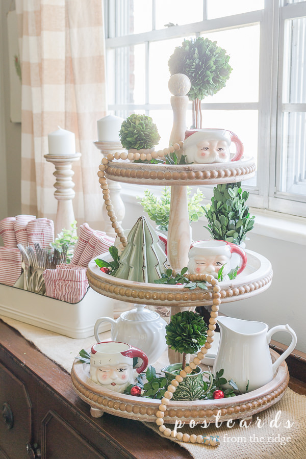 three tiered wooden tray with santa mugs, preserved boxwood topiaries, fresh cut greenery