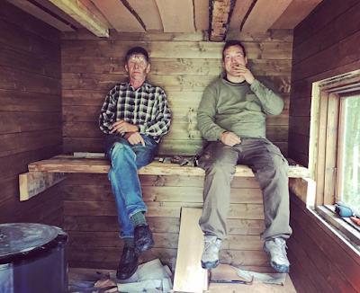 Mies ja isä keskeneräisen saunan lauteilla tupakkatauolla