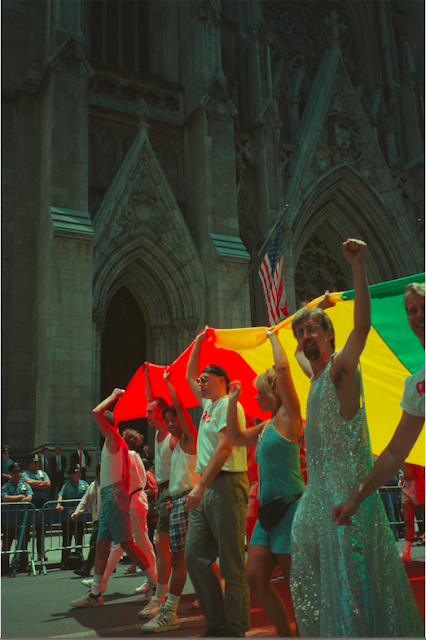 Un grupo de personas marchando por una calle portando una colorida bandera sobre sus cabezas