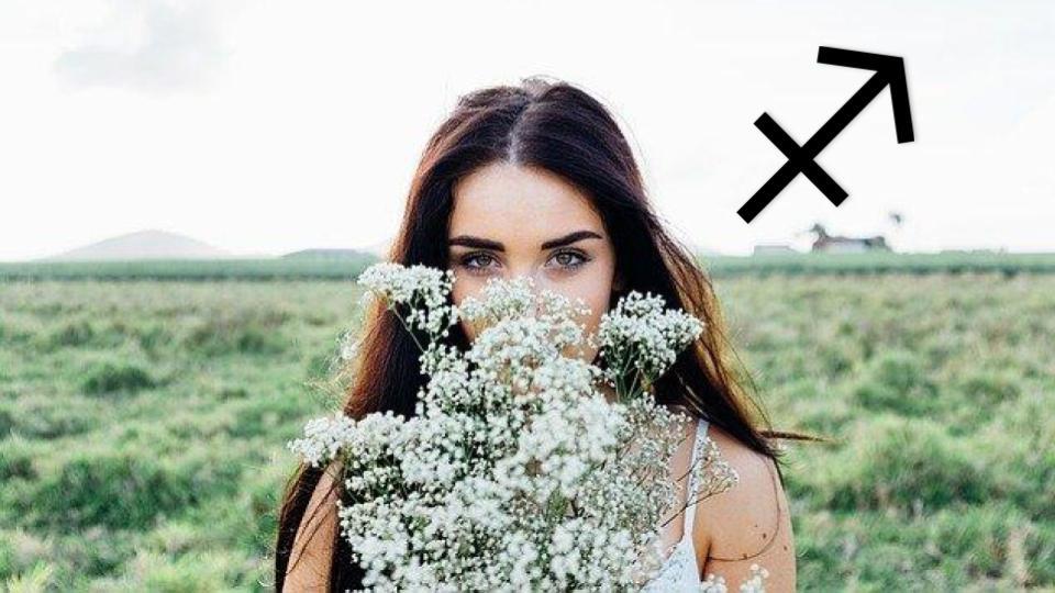 Une femme sagittaire cache son visage derrière un bouquet de fleurs